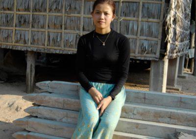 Portrait d'une jeune femme devant sa maison, assise sur des matériaux de construction, village de Sra Srang, province de Siem Reap.