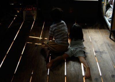 Enfants regardant la télé, allongés au sol dans leur maison, village de Sra Srang, province de Siem Reap.