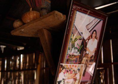 Intérieur d'une maison, photographies de famille encadrées et bâtons d'encens posés autour d'une poutre, province de Kampong Cham.